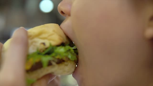 Closeup of female mouth taking a long bite and eating junk unhealthy fast food hamburger