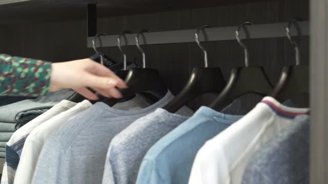 vídeos y material grabado en eventos de stock de un close-up de mujeres asistentes de la tienda de fijación a mano colgadores con diferentes camisetas masculinas en el soporte de metal. demostración de close-up. concepto de tienda de moda de negocios de lujo - moda playera