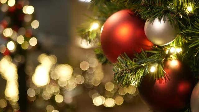 zbliżenie świątecznie zdobione odkryty choinka z jasnymi czerwonymi kulkami na rozmyte musujące tło bajki. rozmyte lampy girlandy, efekt bokeh. wesołych świąt i wesołych świąt koncepcji. - boże narodzenie filmów i materiałów b-roll