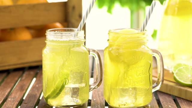vídeos de stock e filmes b-roll de close-up of filling fresh lemonade in mason jar glass on wooden table outside - limonada tradicional