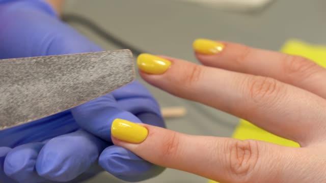 vidéos et rushes de gros plan de correction de forme d'ongle à l'aide de la lime à ongles. vernis jaune. dernière manucure strokes. salon de beauté. - cuticule
