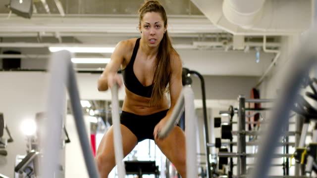 close-up of fit female high-intensity interval training using battle ropes - chudy filmów i materiałów b-roll
