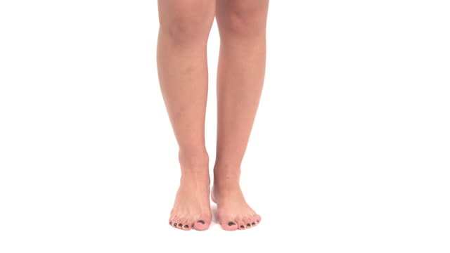 close-up of fit female legs. stylish black pedicure standing on toes. isolated, on white background - pedicure filmów i materiałów b-roll