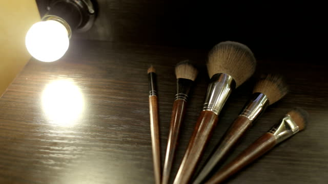 Close-up of five make-up brushes on the table Five professional make-up brushes lie on the table under the light of a lamp. Close-up of five make-up brushes on the table. foundation make up stock videos & royalty-free footage