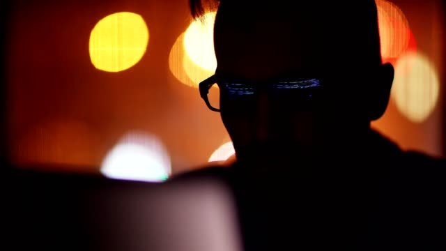 Closeup of focused young programmer in eyeglasses working on laptop computer in dark room at night