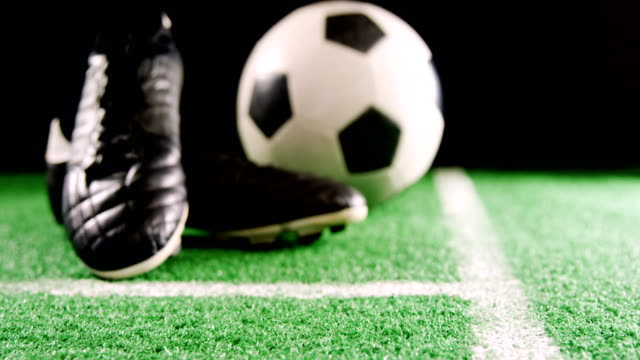 Close-up of football and cleats on artificial grass 4k video