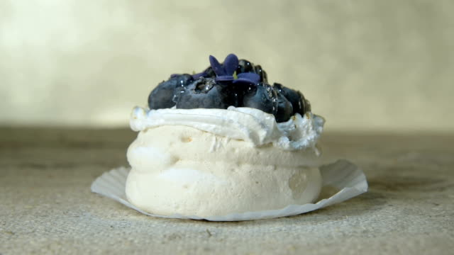 Close-up of fresh delicious airy cake with blueberries on a napkin and moving highlights and glitter