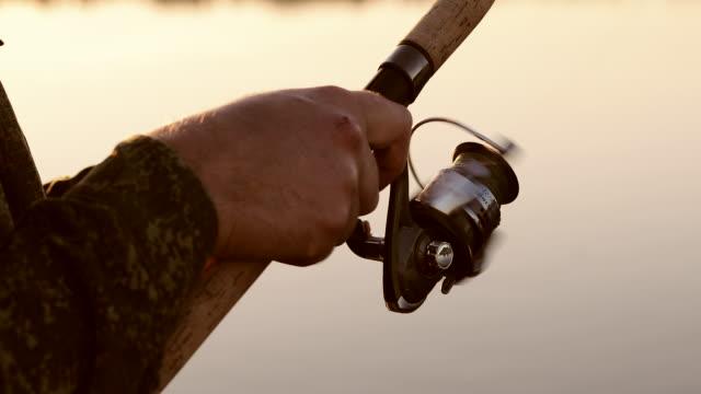 close-up of friction reel fishing rod on the background of a beautiful sunset. - żabnicokształtne filmów i materiałów b-roll