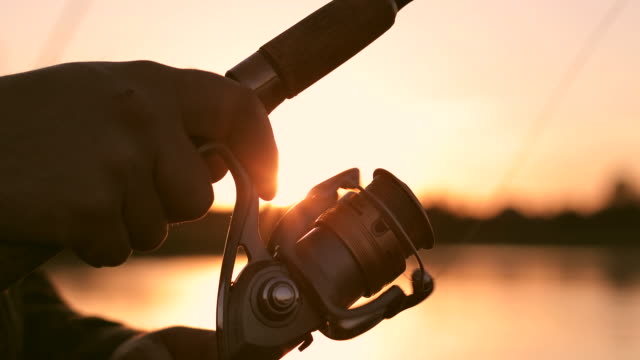 Close-up of friction reel fishing rod on the background of a beautiful sunset. Close-up of friction reel fishing rod on the background of a beautiful sunset. Man actively fishing on the lake or river. fishing rod stock videos & royalty-free footage