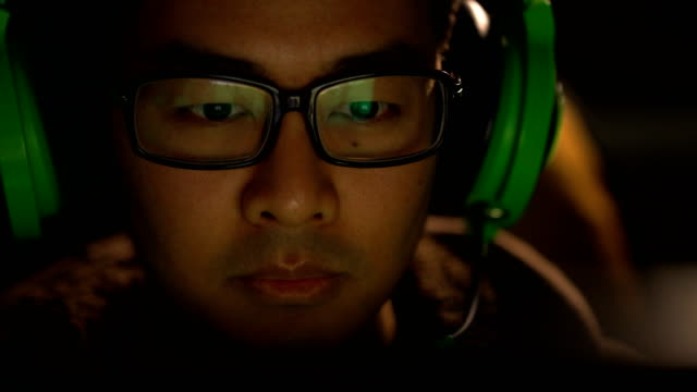 Close-up of gamer wearing eyeglasses playing computer video games