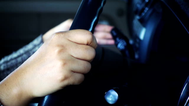 close-up of girl hands on the steering wheel and using turn switch in car. slowmotion shot - leva video stock e b–roll