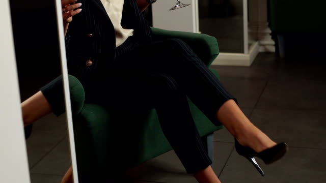 Close-up of girl in striped suit with high heels sitting in a chair with a cigar