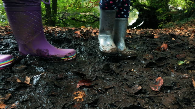 closeup of girls wellington boots playing in a muddy puddle video