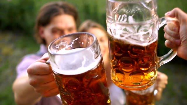 close-up of glasses with beer. celebration at the oktoberfest festival. to clink glasses twice - традиционная одежда стоковые видео и кадры b-roll