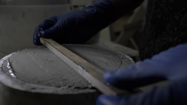 Close-up of gloved hands leveling fresh concrete with a special ruler. wet concrete in silicone form. 4k. 4k video. slow motion. 23.98 fps