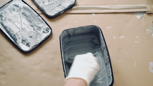 Close-up of gloved hands mixing grey paint or plaster with a spatula