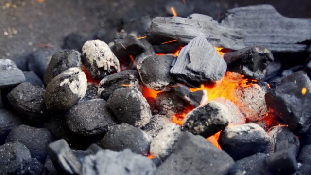 Closeup of glowing coal in metal grill on summer day in slow motion
