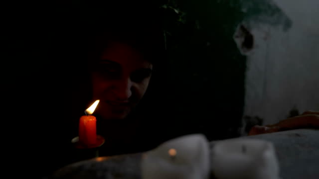 Closeup of gothic woman possessed by a demon snarling and hissing behind candles in a dark chamber video