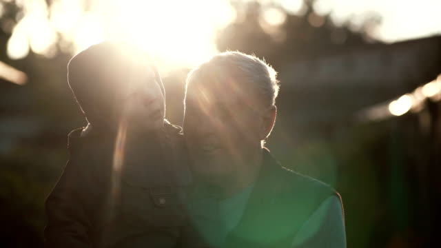 CLose-up of grandfather holding grandson on hands, hugs and kiss boy on cheek. Old man standing outdoor in sunlight. 4K video