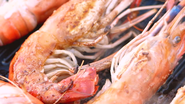 Close-up of grilled fresh shrimps on a picnic stove being to roast in a pan with butter. Camping food.