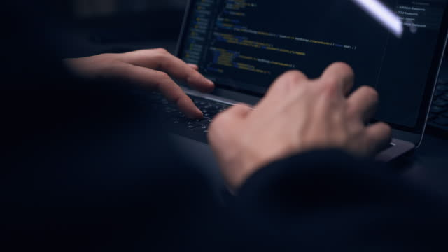 Close-up of hacker's hands typing program code on laptop