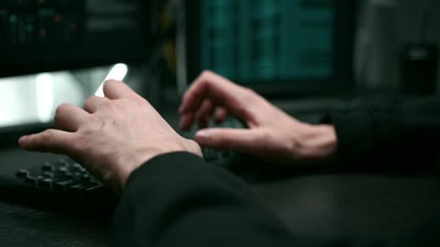 close-up of hacker's hands typing program code on laptop - phishing filmów i materiałów b-roll