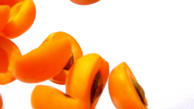 Closeup of halves ripe juicy apricots flying diagonally on a white background - video