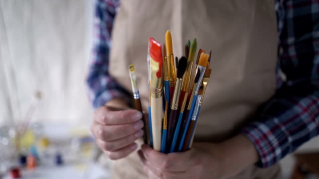 close-up of hand artist with brushes. canvas stands on the easel. the artist draws at the easel. - eastern european descent stock videos & royalty-free footage