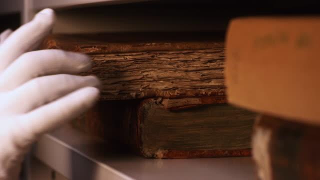 博物館や私立図書館の本棚から非常に古い本を取る白い綿の手袋で手のクローズアップ。ストック映像。古代の黄色い本の探索 ビデオ