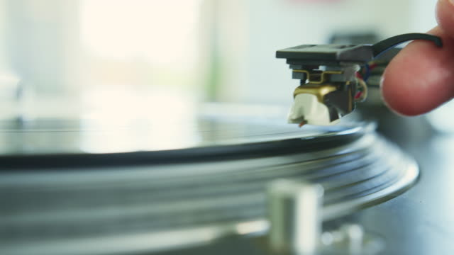 closeup of hand placing stylus needle on record player - giradischi video stock e b–roll