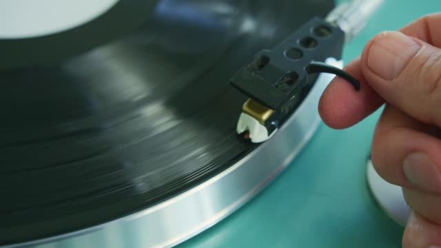 Closeup Of Hand Placing The Stylus Needle On Record