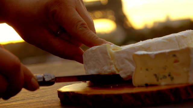 カマンベール チーズを取る手のクローズ アップ - フランス料理点の映像素材/bロール