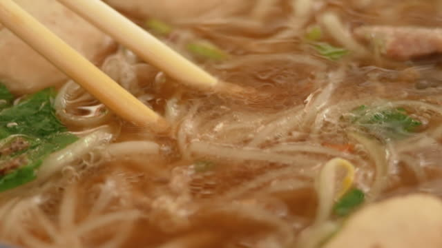 Close-up of hand use chopstick to pick noodles in a traditional Vietnamese beef soup Pho. Vietnamese style food.