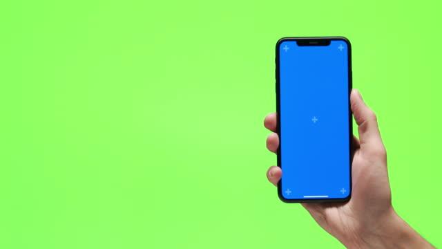 vidéos et rushes de plan rapproché de la main utilisant le smartphone avec l'écran vert pour le montage d'affichage graphique - photophone