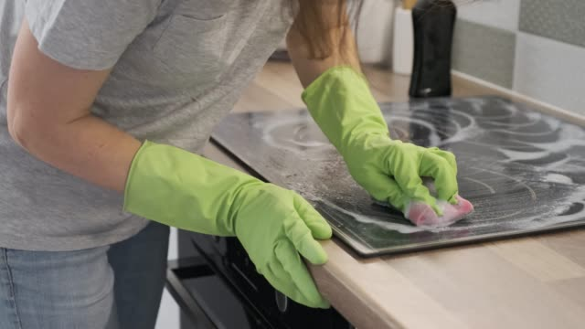 closeup of hand woman cleaning modern cooking glass ceramic electric surface with sponge and detergent - fornello video stock e b–roll