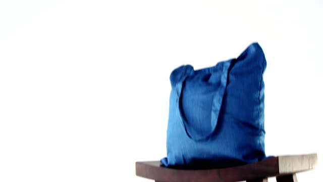 Close-up of handbag on stool Close-up of handbag on stool against white background fabric swatch stock videos & royalty-free footage