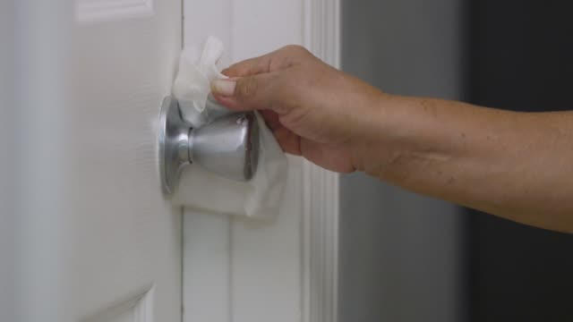 Close-up of hands cleaning a door handle during quarantine video