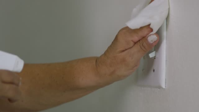 Close-up of hands cleaning light switch during quarantine video