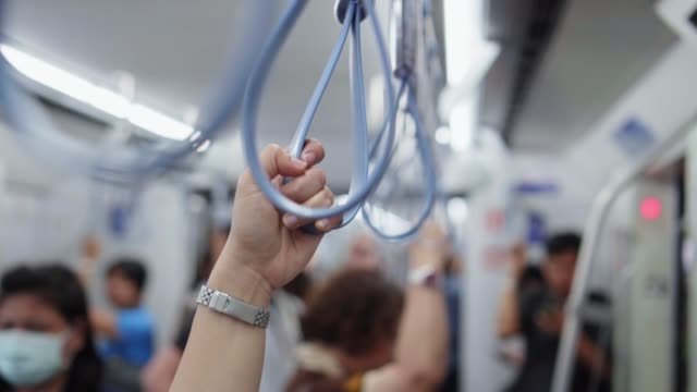 close-up of hands holding handrail or grip straps in metro train,slow motion - parapetto barriera video stock e b–roll
