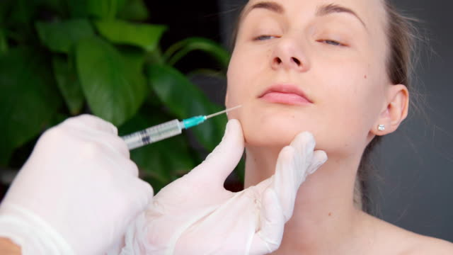 Close-up of hands of cosmetologist making botox injection to female lips. Young woman gets facial injections in salon. video