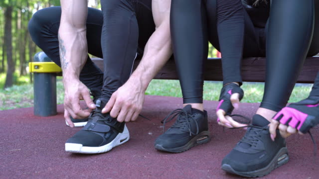 Close-up of hands of man and woman tying shoelaces on sneakers before training outdoors