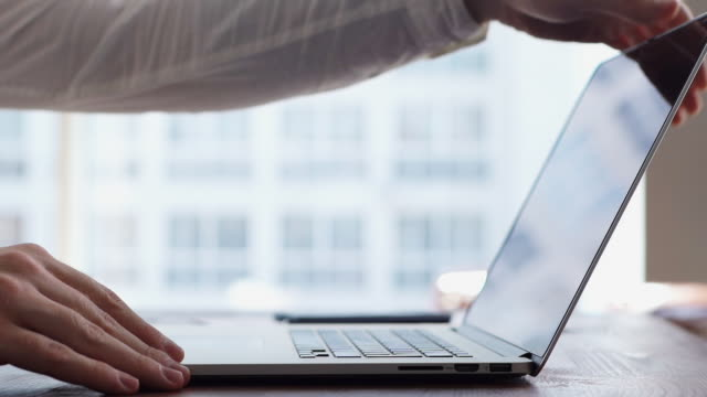 Close-up of hands of unrecognizable man turning off laptop and closing lid.
