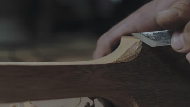 nahaufnahme der hände, die ein holzprodukt mit einem messer schneiden. ein zimmermann verarbeitet einen holzbalken mit einem messer. 4k video. 59,94 fps - tischlerarbeit stock-videos und b-roll-filmmaterial
