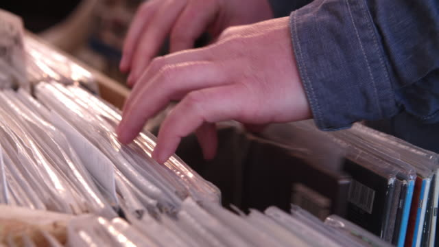 Close-up of hands sorting through records at a record shop video