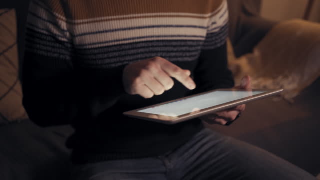 Close-up of hands typing on a digital table late at night indoors