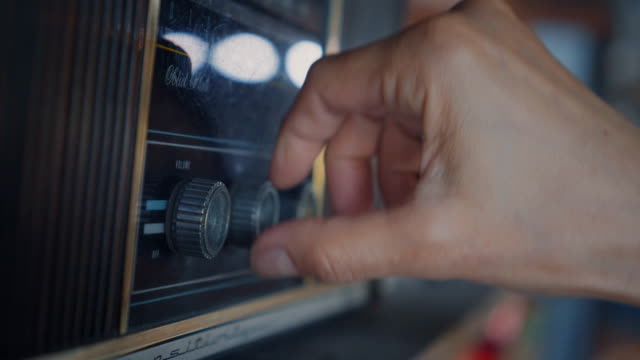 Close-up of hands using analog vintage radio