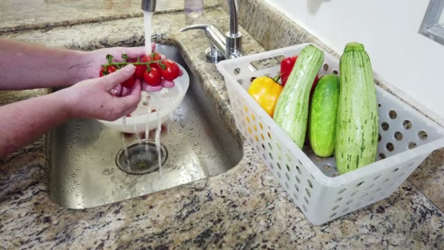 Close-up of hands, washing vegetables (tomato) in domestic kitchen sink