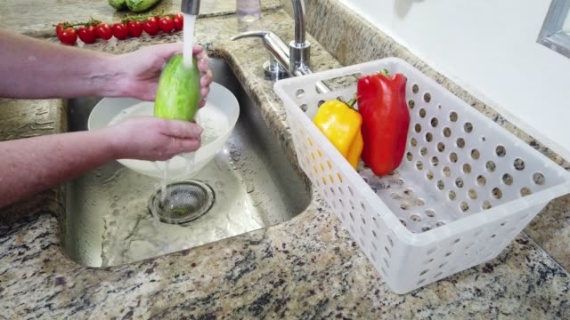 Close-up of hands, washing vegetables (cucumbre) in domestic kitchen sink