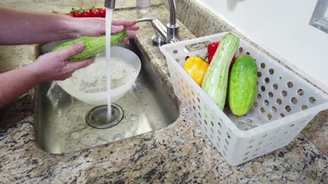 Close-up of hands, washing vegetables (zucchini) in domestic kitchen sink