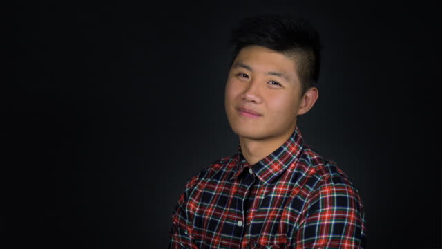 Close-up of happy handsome young man blinking Portrait of confident male smiling against black background. Close-up of happy handsome young man is blinking. He is in plaid shirt. east asian ethnicity stock videos & royalty-free footage